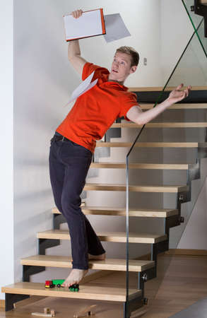 inattentive: Young inattentive man slipping on stairs on a toy