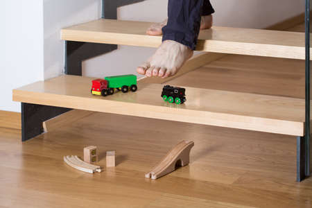 untidiness: Close-up of mans foot stepping on toys on stairs Stock Photo