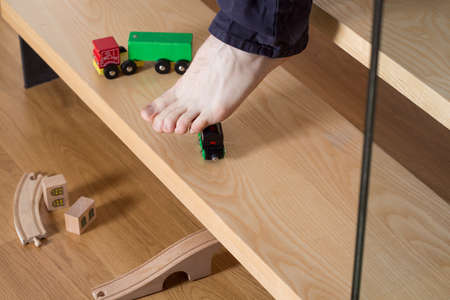 stumbling: Close-up of young mans foot on stairs stepping on boys toy Stock Photo
