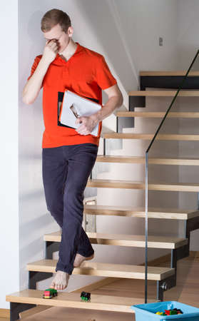 clumsy: Young sleepy man doesnt see toys on stairs Stock Photo