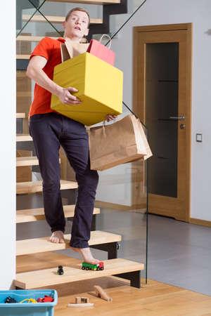 重い箱を持って階段で不注意な青年