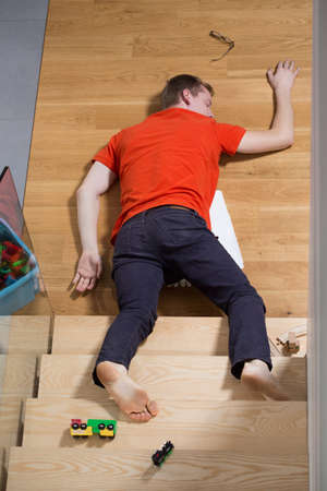 lying down on floor: Young unconscious man lying down on the stairs