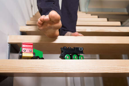 Close-up of man's foot and toys left on steps