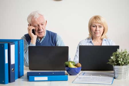 hombres trabajando: Pares ocupados uso de ordenadores port�tiles para trabajar en la oficina en casa Foto de archivo