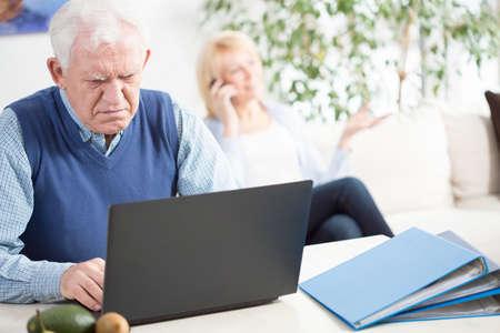 transact: Worried elder man working on laptop at home Stock Photo