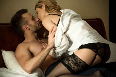 young couple sex: Молодая страстная пара во время прелюдии в постели Фото со стока