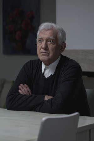 hombre solitario: Triste hombre solitario anciano sentado en casa