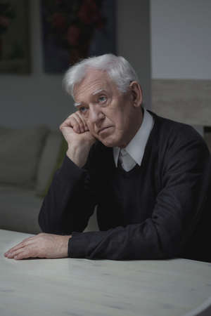 Older depressed man thinking about his past photo
