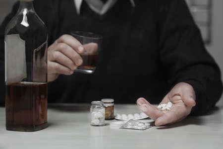 persona deprimida: Primer plano de hombre mayor se toma sus medicamentos con alcohol