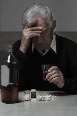 Senior depressed man drinking alcohol and taking drugs photo