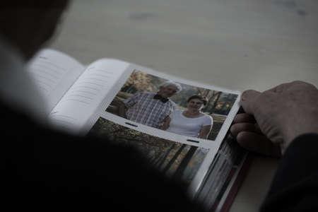 Close-up of older man browsing his photo album photo