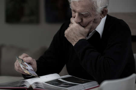 Senior sad man with photo missing his wife