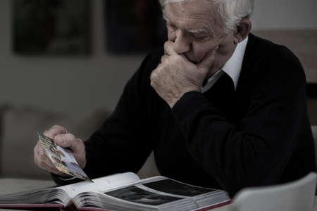 hombre solo: Hombre mayor triste con la foto que falta a su esposa Foto de archivo