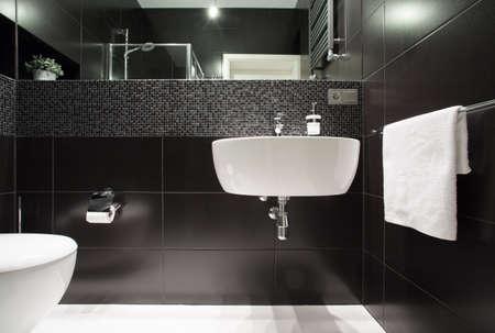 モダンなバスルームの黒い壁に白い洗面器 写真素材