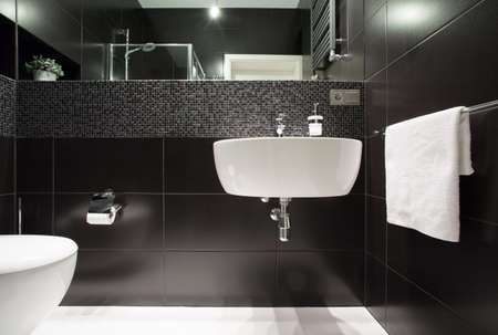 bathroom tile: White basin on black wall in modern bathroom