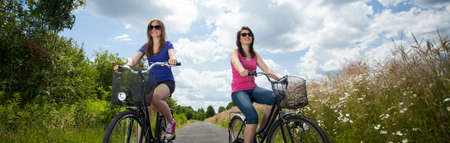 free riding: Two girls on summer bicycle trip in country