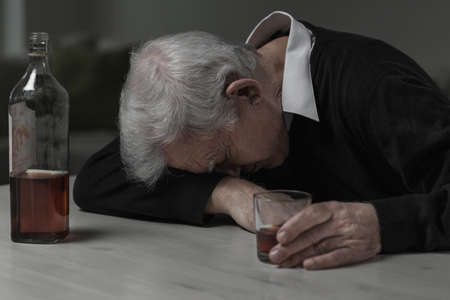 drinking drunk: Senior man sleeping after drinking too much alcohol Stock Photo