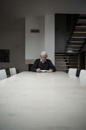 Photo of single older man eating dinner alone at home photo