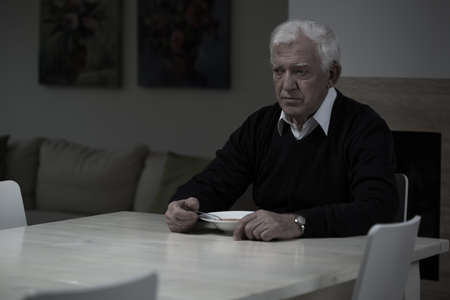one senior: Aged depressed man and his lonely dinner Stock Photo