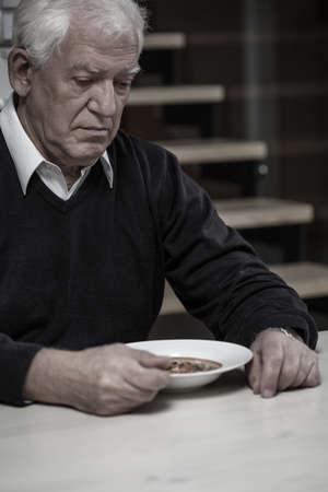 Older depressed alone man eating dinner at home photo