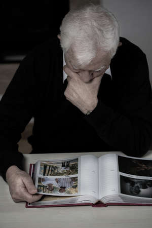 old photo album: Older man with photo album recollecting old times