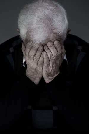 Portrait of aufgeschlüsselt älteren Mann versteckt das Gesicht in die Hände