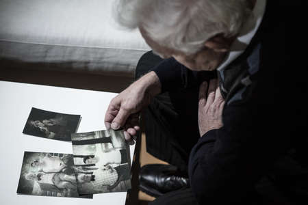 Senior depressieve man op zoek naar oude foto's Stockfoto
