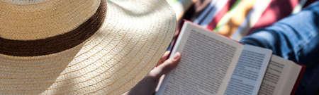novel: Woman reading a summer novel on a hammock
