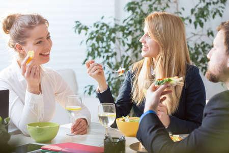 Junge Leute beim Mittagessen in der Pause im Amt Standard-Bild