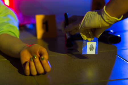 forensic medicine: Close-up of crime scene investigator collecting evidence