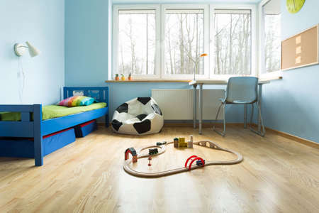 boy bedroom: Blue painted walls in designed boys room