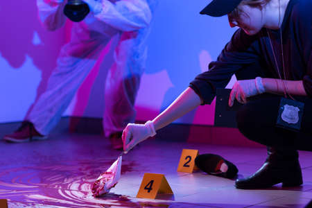 Image of policewoman working on a murder scene Stock Photo