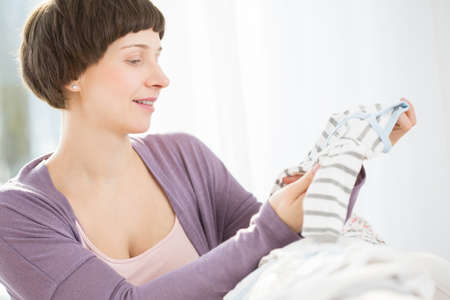 birthing: Expectant mother watching cute clothes for baby Stock Photo