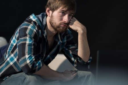 ソファーに座って若い無職の男