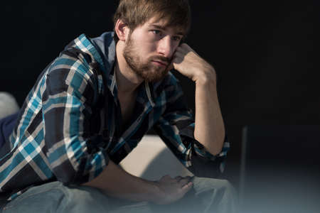 Young unemployed man sitting on the sofa