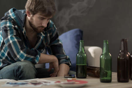 addiction alone: Picture of young alcoholic drinking beers alone Stock Photo