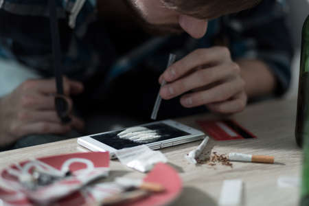 sniffing: Close-up of drug addicted man taking cocaine