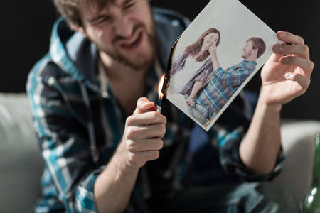 Angry young man burning photo with ex-girlfriend