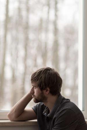 homme triste: Sad jeune homme assis à la fenêtre