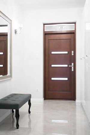 Foto de la puerta de entrada de madera en un gran pasillo blanco