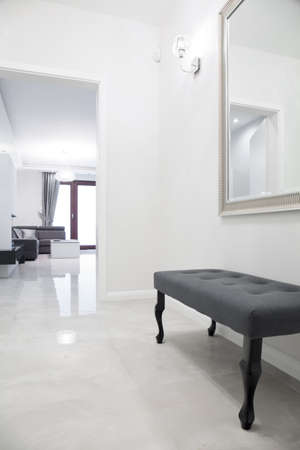 White anteroom with marble floor and gray bench photo