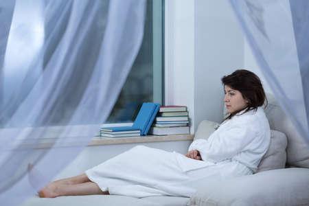 femme triste: Sad woman couch� sur le lit en robe