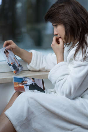 split up: Young depressed woman looking at pictures of ex-boyfriend