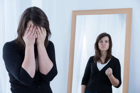 dissimulation: Woman and her true angry reflection in the mirror