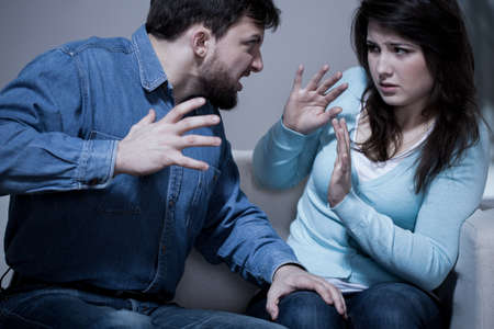 angry person: Angry aggressive husband trying to hit his wife