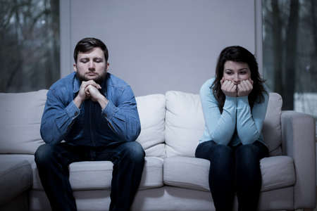 Couple after argument sitting on the sofa 스톡 콘텐츠