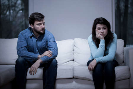husband: Young worried couple sitting on the couch