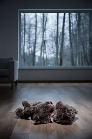 violencia intrafamiliar: Oso de peluche acostado en el piso de madera Foto de archivo
