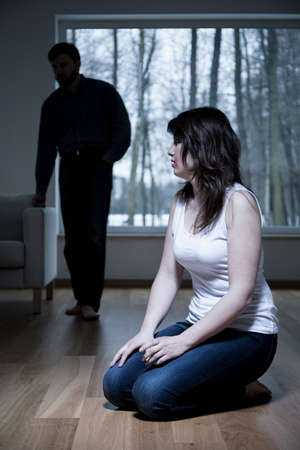 beaten woman: Victim of domestic violence kneeling on the floor