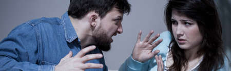 Aggressive man arguing with scared wife - panorama